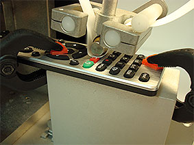 Detail of RCA Abrasion Wear Tester testing a remote control keypad